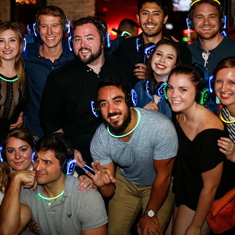 Group of people wearing glowing headphones